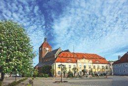 Sie sehen den gut erhaltenen Marktplatz von Rügenwalde mit dem rathaus, dem Hemptenmacherbrunnen und der Marienkirche
