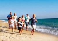 Sie sehen eine Familie in ihrem urlaub an der Ostsee in Polen - sie läuft am Strand entlang